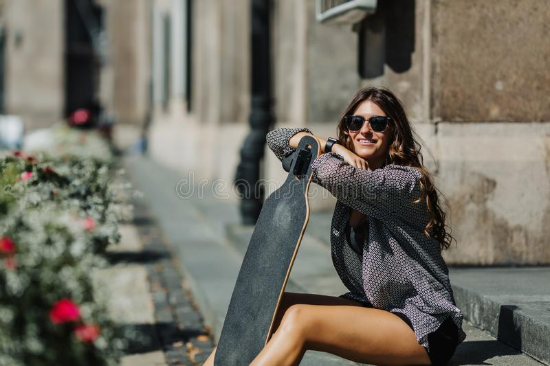 Portrait of Beautiful young woman sitting on the ground and holding a longboard in the city street sunny weather. Young stock image