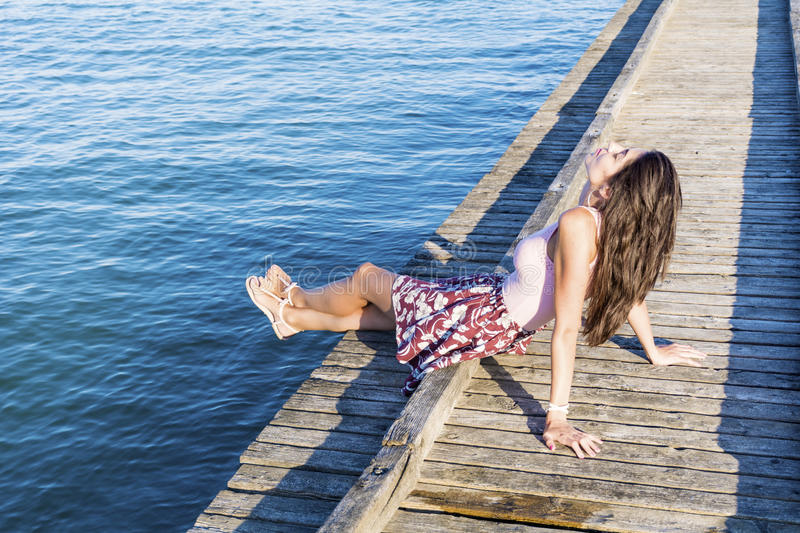 Portrait of beautiful young woman sitting on a wooden pier royalty free stock photo