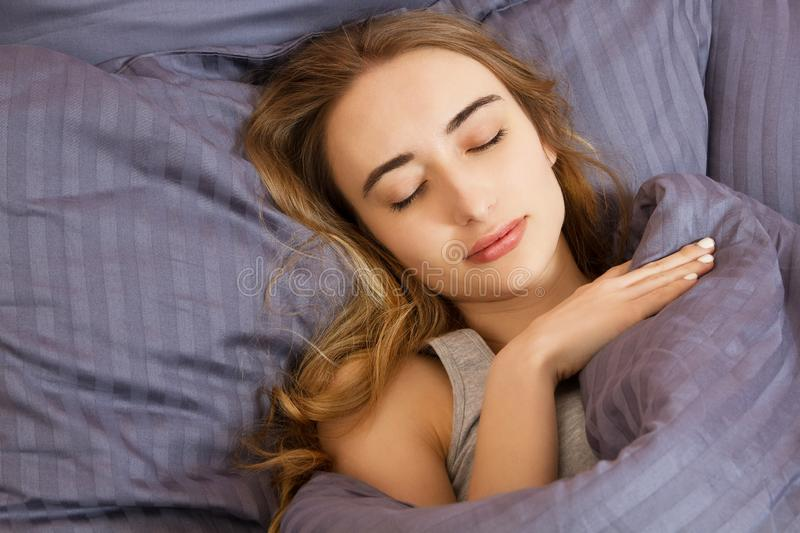Portrait of Beautiful young woman sleeping while lying in bed comfortably and blissfully - sun shines from the window on her face stock images
