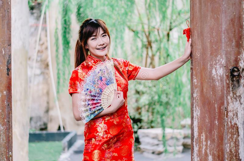 Portrait beautiful young woman smile wear cheongsam deep red dress holding a fan looking camera. Festivities and Celebration stock photos