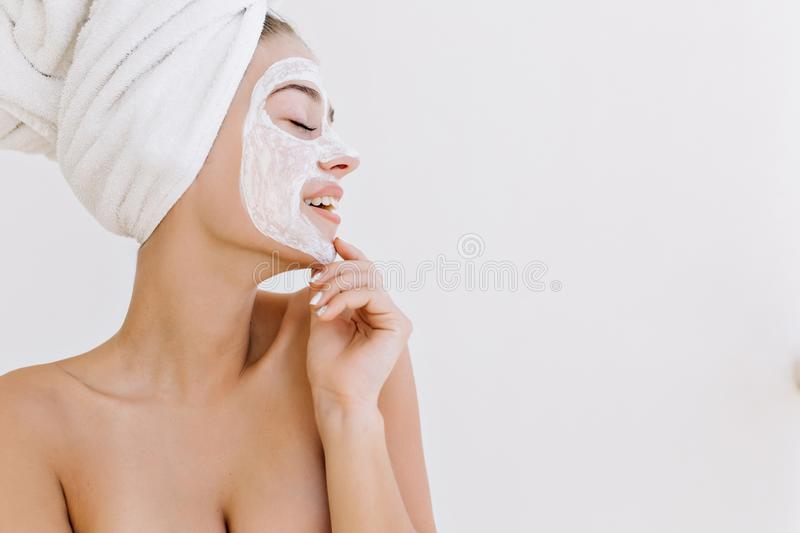 Portrait of beautiful young woman smiling with towels after take bath make cosmetic mask on her face. Rejuvenation royalty free stock photos