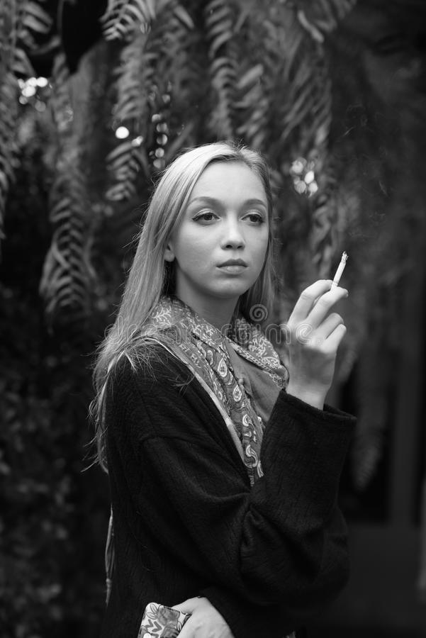 Portrait of a beautiful young woman smoking cigarettes stock photo
