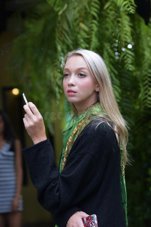 Portrait of a beautiful young woman smoking cigarettes royalty free stock photos