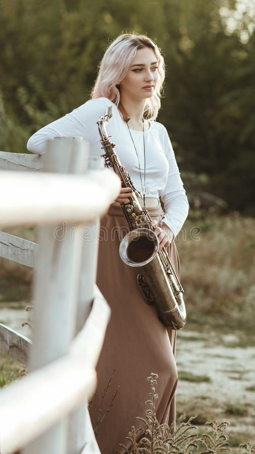 Portrait of a beautiful young woman standing and leaninf on wooden white fence with saxophone, romantic blonde girl relaxing on royalty free stock photos