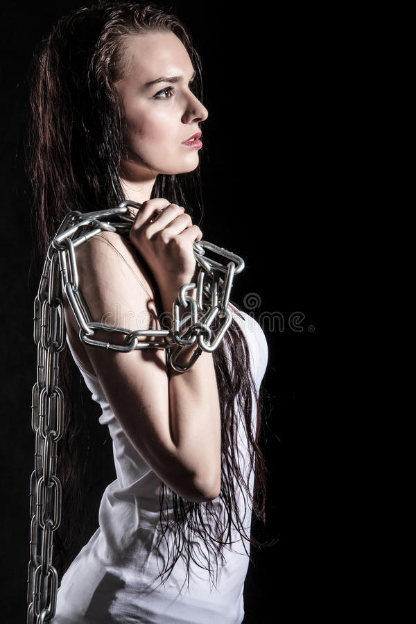 Portrait of a beautiful young woman with a steel chain. Over black background stock photos
