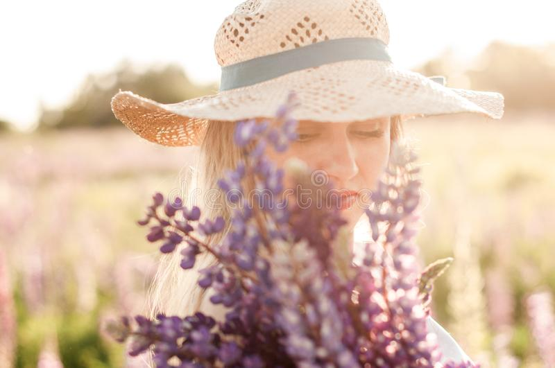 Portrait of a beautiful young woman in a straw hat with a bouquet of plucked lupins. At sunset stock photo