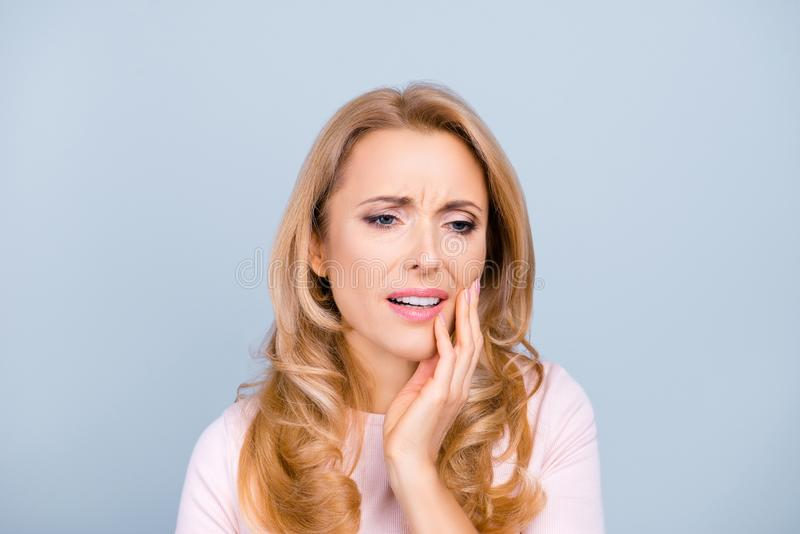 Portrait of beautiful, young, woman suffering from terrible strong teeth pain, touching cheek with hand over grey background, too stock image