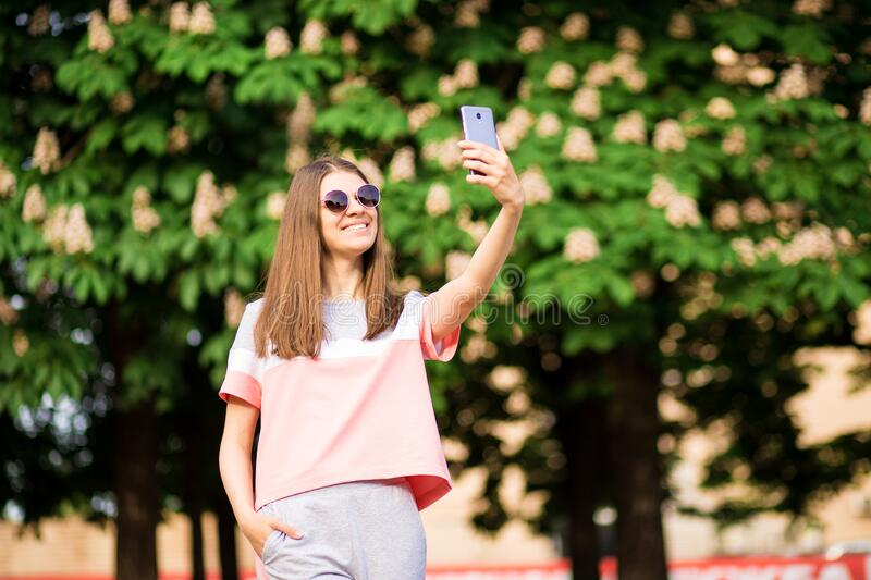 Portrait of beautiful young woman in sunglasses take selfie in park with smartphone. With chestnut on background royalty free stock photography