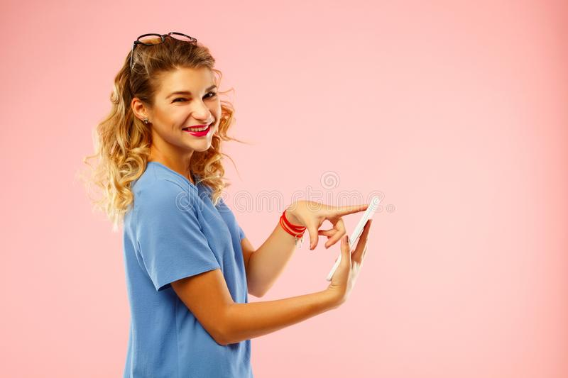 Portrait of a beautiful young woman with tablet over pink background royalty free stock image