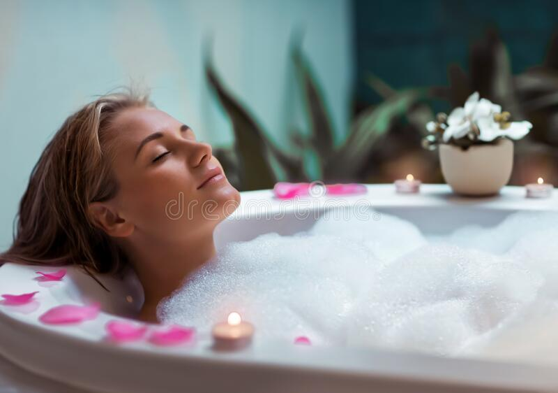 Enjoying dayspa. Portrait of a beautiful young woman taking bath with foam by candlelight, enjoying dayspa in luxury spa hotel stock photos