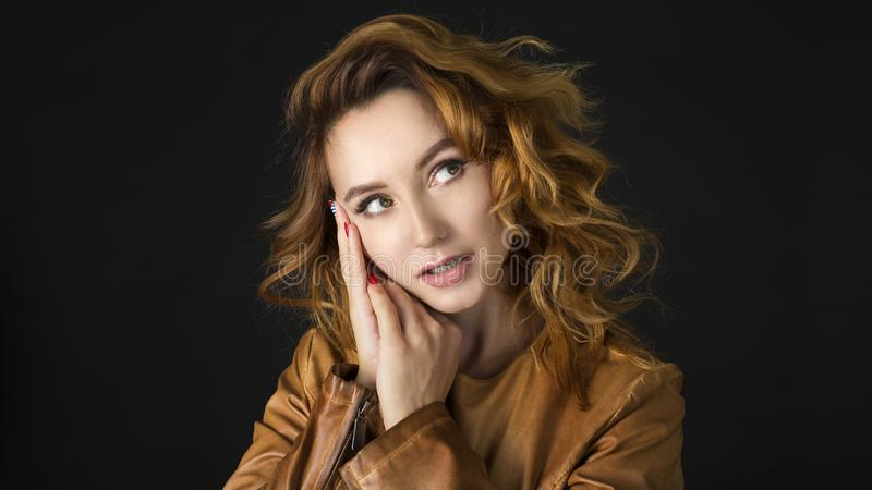 Portrait of a beautiful young woman thinking, on dark background royalty free stock photo