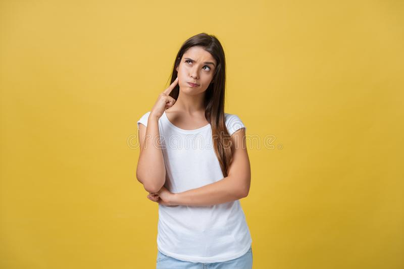 Portrait of a beautiful young woman thinking, isolated on yellow background stock photos