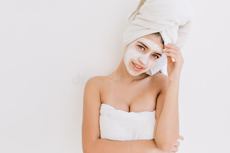 Portrait of beautiful young woman with towels after take bath make cosmetic mask on her face. Rejuvenation, cosmetology stock photo