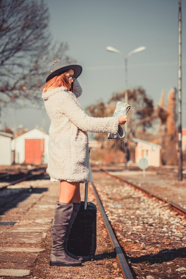 Young woman with luggage on train station royalty free stock images