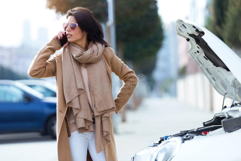 Beautiful young woman using her mobile phone calls for assistance for car. Portrait of beautiful young woman using her mobile phone calls for assistance for car stock images