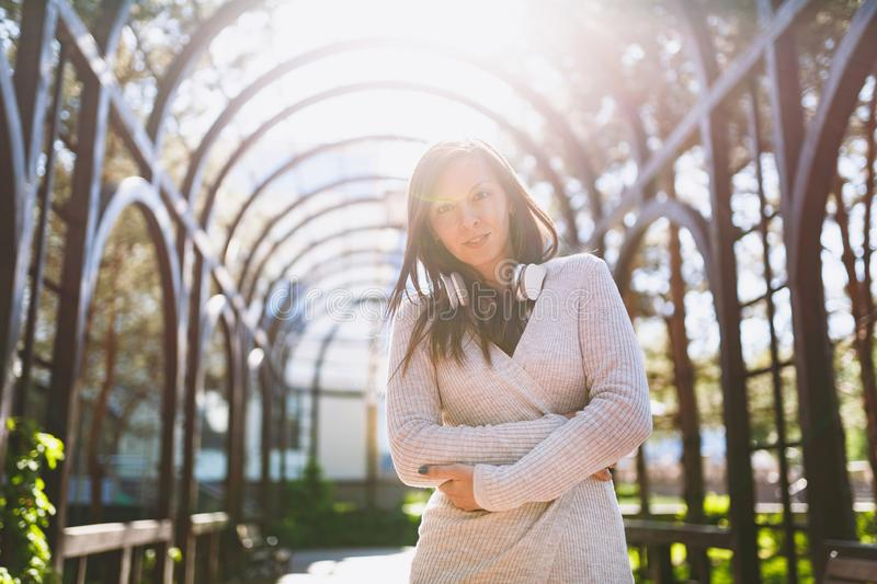 Portrait of beautiful young woman wearing light casual clothes. Girl standing under sunshine archway with headphones on stock photo
