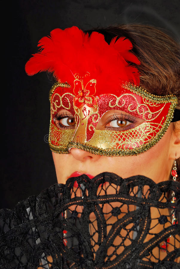 Portrait of beautiful young woman wearing red mask
