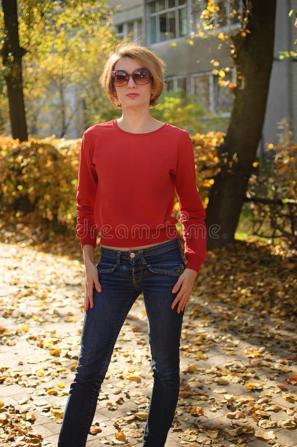 A portrait of a beautiful young woman wearing sunglasses, red sweater and dark jeans in a sunny autumn urban park royalty free stock photos