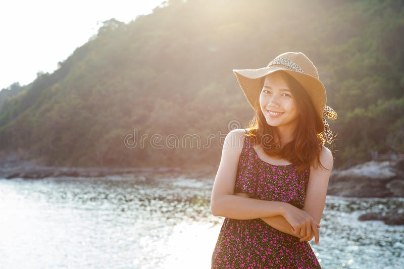 portrait of beautiful young woman wearing wide straw hat standing beside sea beach and toothy smiling face wtih happy emotion stock photography