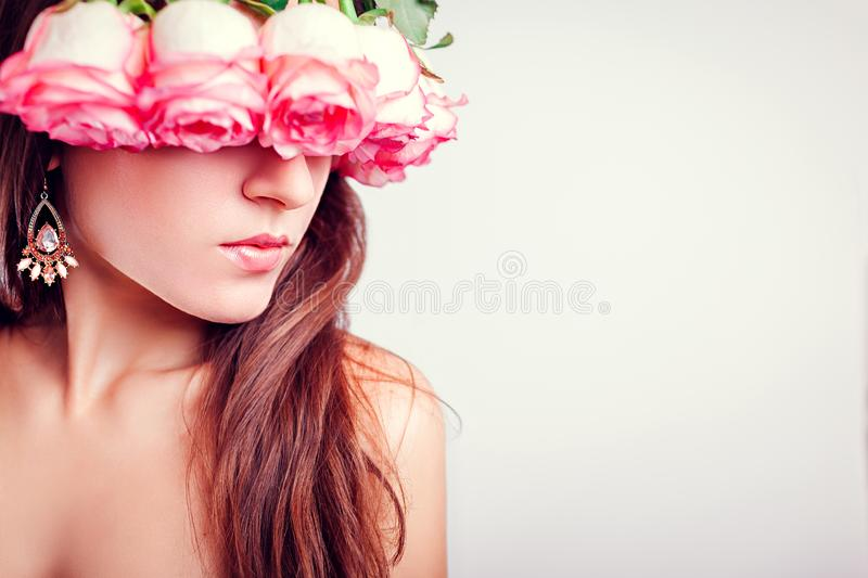 Portrait of beautiful young woman wearing wreath made of roses. Beauty fashion concept. Healthy skin and hair stock photo