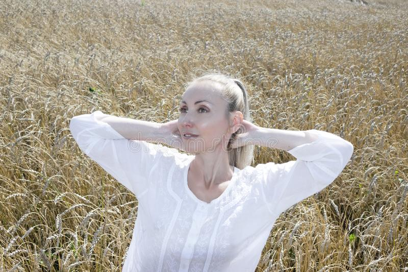 Portrait of a beautiful young woman in a white blouse with long blond hair in a field of golden wheat ears on a summer day royalty free stock images