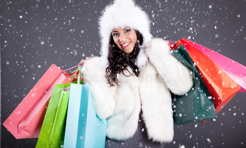 Portrait of a beautiful young woman in a white fur coat holding stock photography