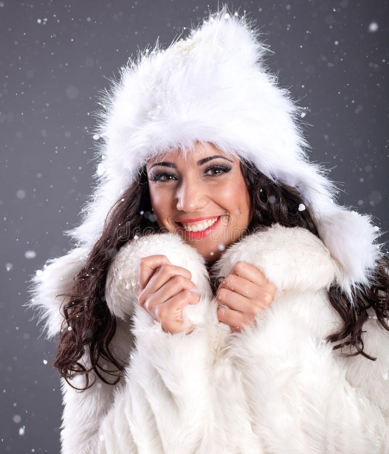 portrait of a beautiful young woman in a white fur coat over snowy Christmas background stock photography