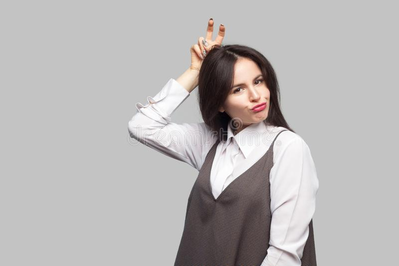 Portrait of beautiful young woman in white shirt and brown apron with makeup and brunette hair standing doing funny face and stock photography