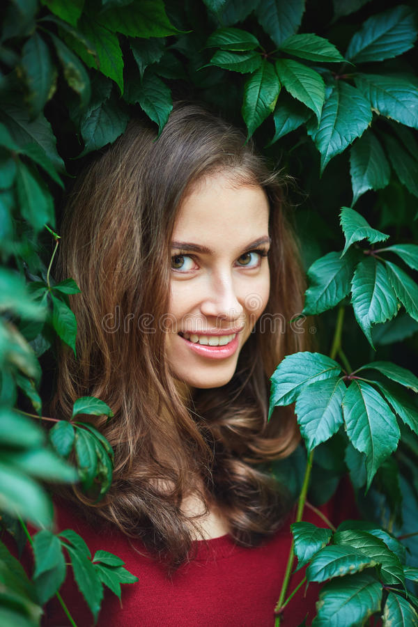 Portrait of beautiful young woman in wild leaves royalty free stock photo