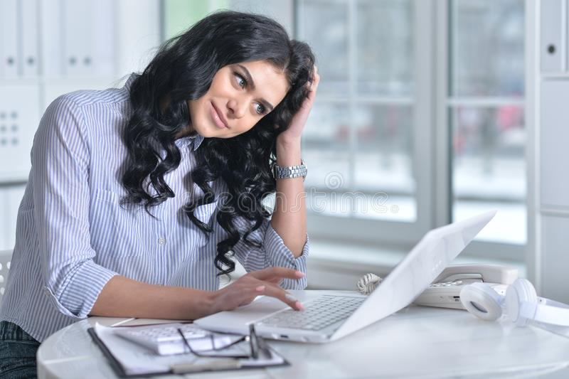 Portrait of a beautiful young woman working in modern office royalty free stock photo