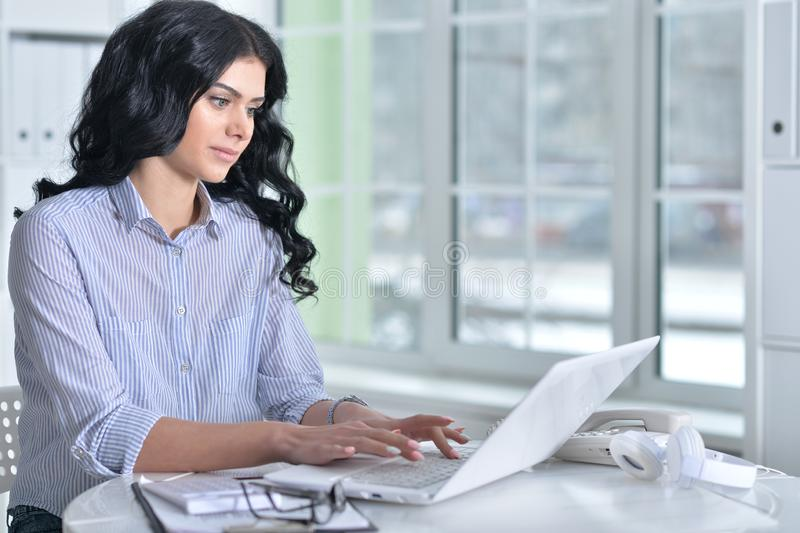 Portrait of a beautiful young woman working in modern office stock image