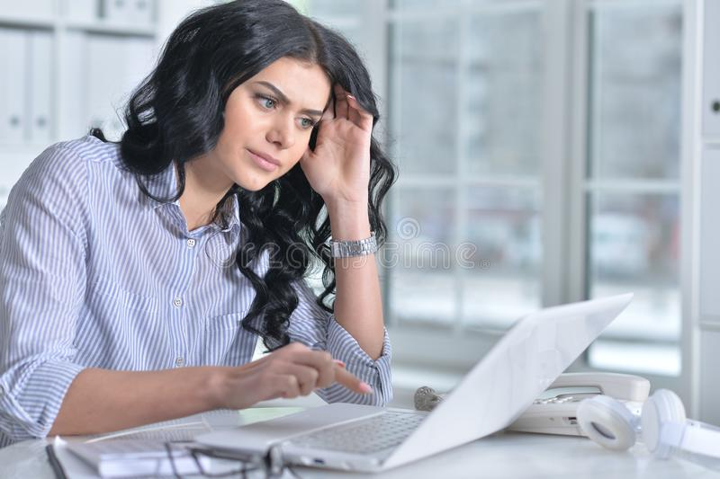Portrait of beautiful young woman working in office royalty free stock image
