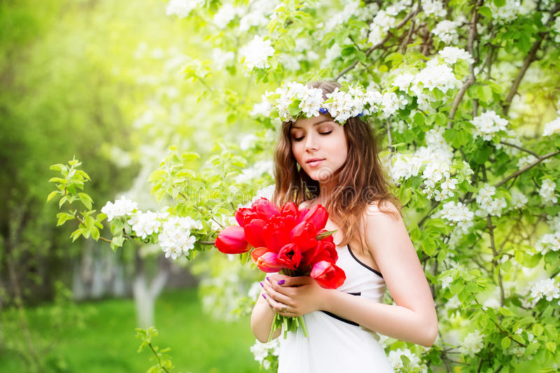 Portrait of a beautiful young woman in a wreath of spring flower royalty free stock images