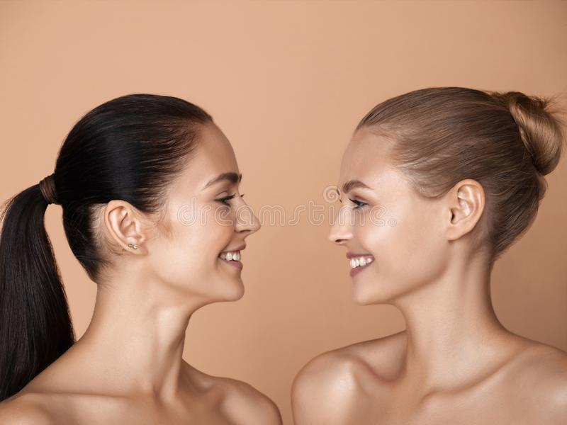 Portrait of beautiful young women isolated on brown studio background royalty free stock photography