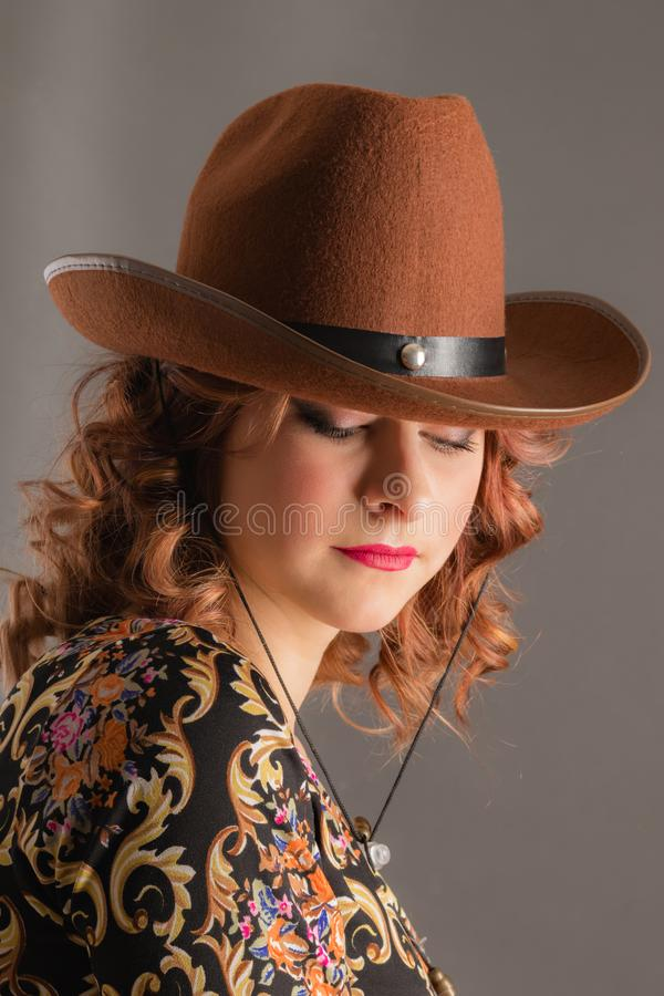 Portrait of an attractive girl with lowered eyes in a cowboy hat stock images