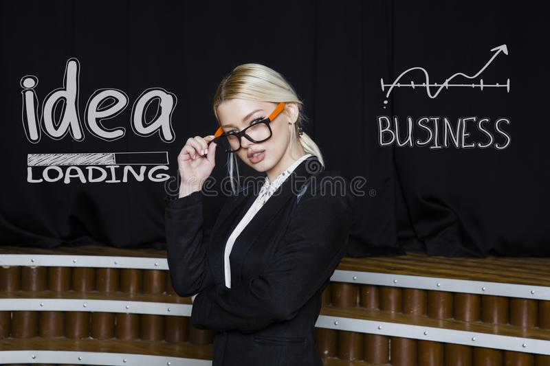 Portrait of a beauty blond busiensswoman in a black suit standing near white sketchs. Portrait of a young beauty blond busiensswoman in a black suit standing royalty free stock photos