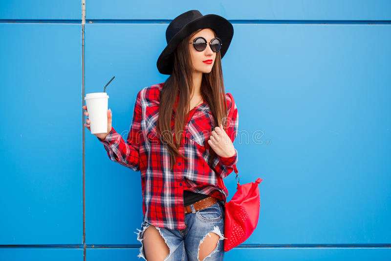 Portrait of beauty fashion smiling woman with coffee in sunglasses on blue background. Outdoor. Copy-space. Red bag. Portrait of beauty fashion smiling woman royalty free stock photography