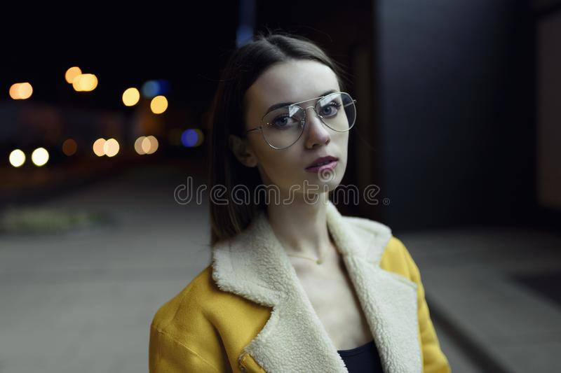 Portrait of female model in stylish jacket and glasses. Her face is lit by city center lights by night. Womenswear fashion royalty free stock photography
