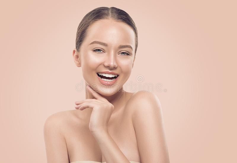 Portrait of beauty smiling young woman on beige background. Beautiful spa girl with perfect fresh skin proposing a product. Cleansing, skincare concept stock photos