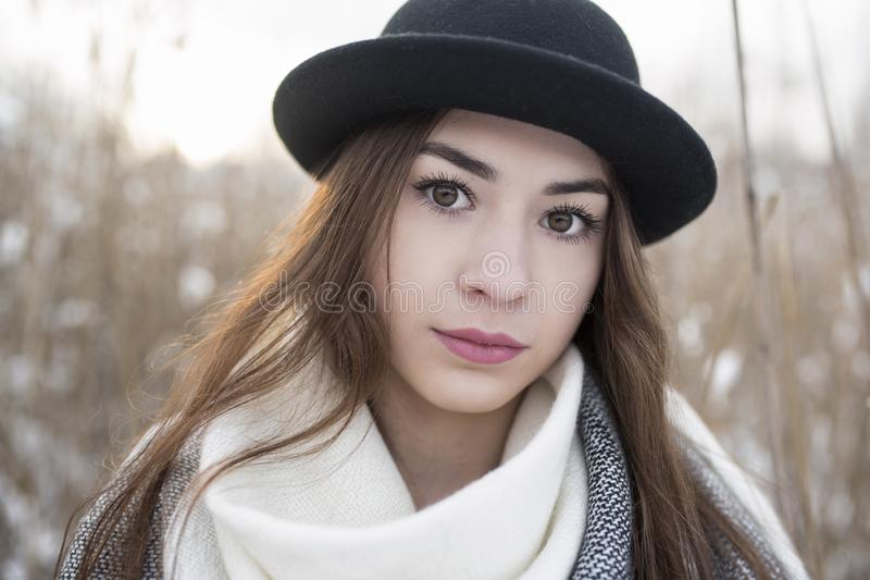 Portrait of beauty woman with big brown eyes, and bowler hat on, in winter scenery stock photography