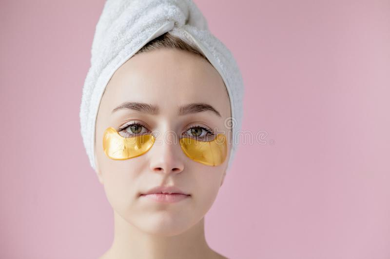 Portrait of Beauty Woman with Eye Patches on pink background. Woman Beauty Face with Mask under Eyes. Beautiful Female with stock images