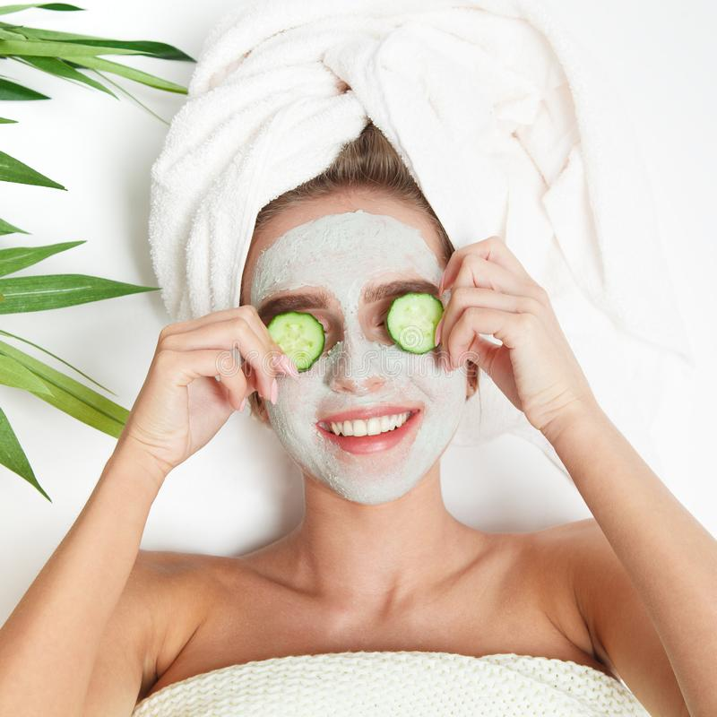 Portrait of beauty woman laying with towel on the head, cucumber on her eyes, facial mask. Spa therapy. Relax. royalty free stock photography