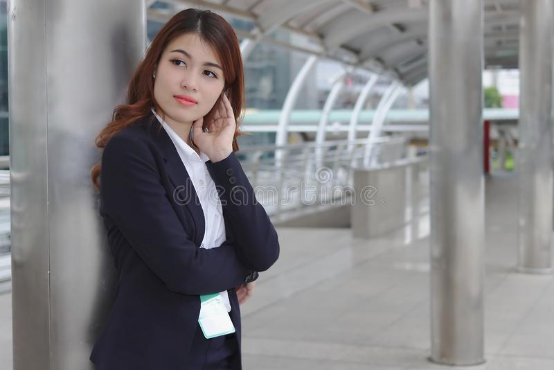 Portrait of beauty young Asian businesswoman in suit standing and looking at far away. Thinking and thoughtful business concept stock photo