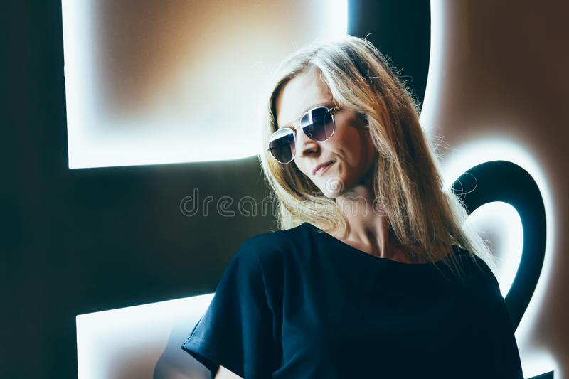 Portrait of beauty young blonde hair woman with neon light and sunglasses. Night life.  royalty free stock photo