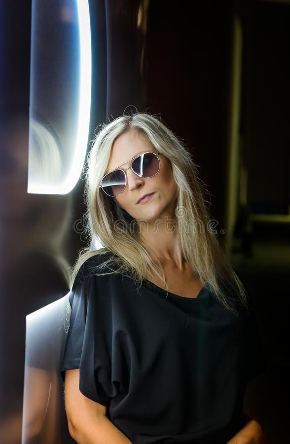 Portrait of beauty young blonde hair woman standing near neon light with sunglasses. Night life.  royalty free stock image
