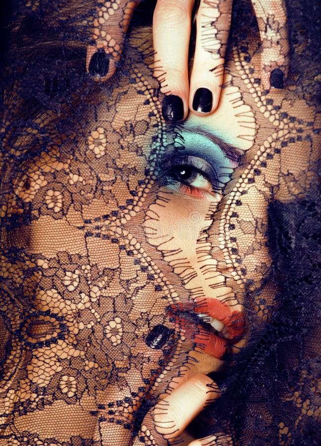 Portrait of beauty young woman through lace close up mystery mak. Eup fashion stock photo