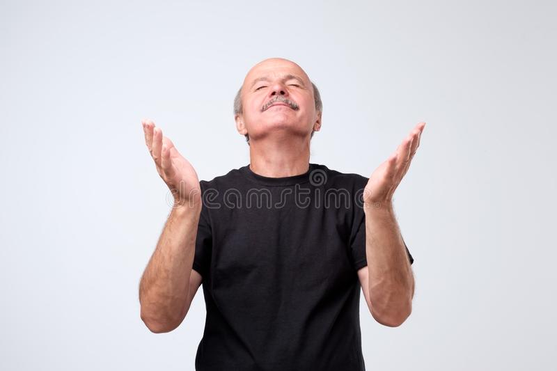 Portrait of begging caucasian man in casual outfit, holding hands in pray and looking up hopefully, praying. Or making with, asking god favour or mercy royalty free stock image