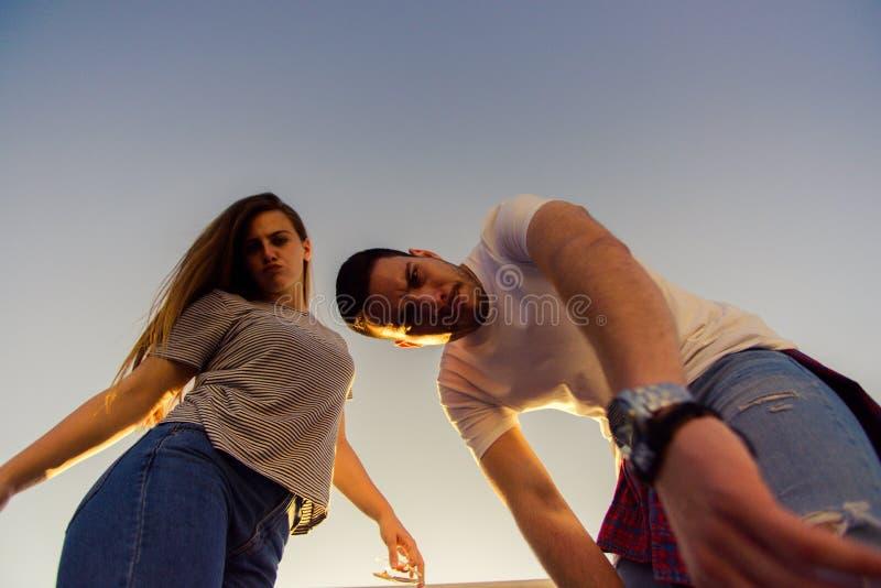 Portrait from below of two best friends on blue sky royalty free stock photo