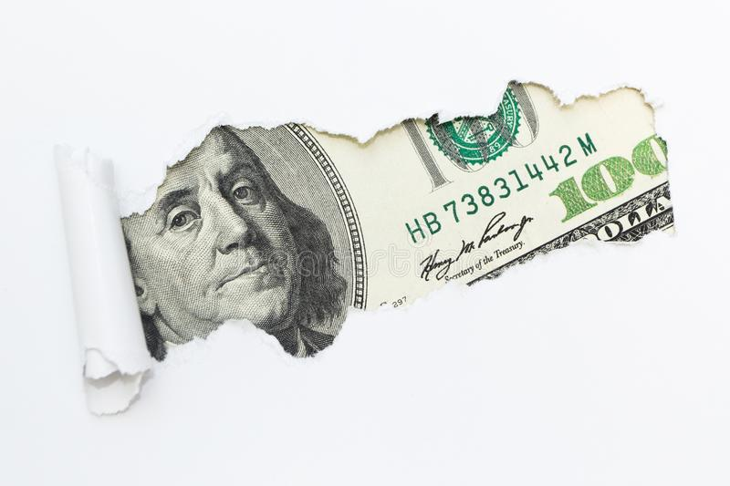 Portrait of Benjamin Franklin on a hundred dollar bill in the gap hole of a white background. Dirty money, illegal income. stock photos