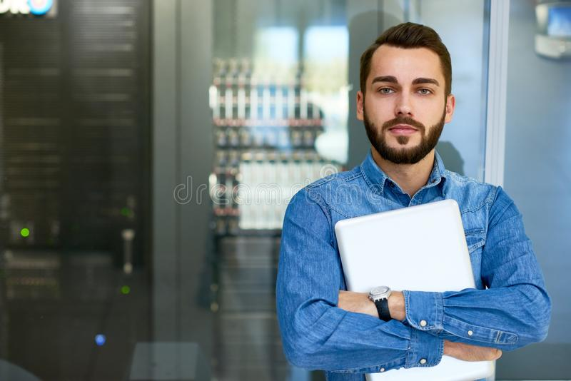 Portrait of Systems Administrator. Portrait of beraded systems administrator posing holding laptop and looking at camera standing against server cabinet, copy royalty free stock image